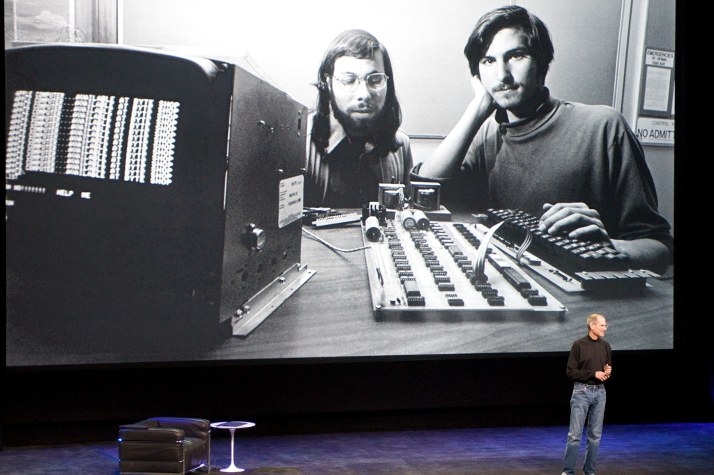 Steve Jobs speaks in front of a photo of him and Apple co-founder Steve Wozniak. Photo by Jeff Carlson.