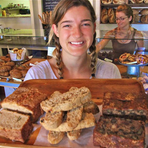 Taylor Strand offers up biscotti and more at Companion Bakery, with Katrina Gimbel in the background.