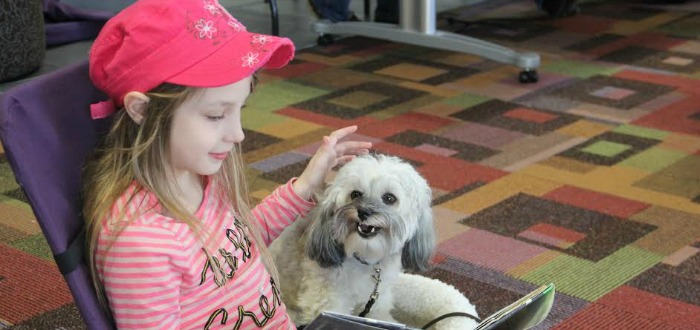 Victoria Victor reads to Saide, one of the Santa Cruz Libraries' Taies to Tails dogs. Photo by Chip Scheuer.