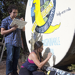 Irene O'Connell and Brandon Hayward work on a mural at UCSC. (Photo by Georgia Perry)